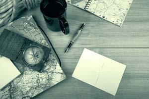 Flat lay of notepad with a map and compass.